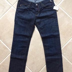 """Varetype: Nye fede jeans fra Replay. Replay Jeans med 3/4 ben. Farve: Blå Oprindelig købspris: 1400 kr.  Rigtig fede NYE jeans fra Replay And Sons.  Jeg syntes de har et fedt snit og fede detaljer. Benene stumper lidt, hvilket er moderne for tiden, hvor man også ruller dem lidt op.  Fede sommer og forår, men også vinter, til støvler.   Der står """"32"""" og """"142 cm"""" inde i dem. MÅL: Hvis du kigger på billedet af livet, så går de ned i en """"trekant"""" foran, hvilket giver en større livvidde end målt lige over.  Lige over bagpå = 35 cm. Hver """"spids"""" = 19 cm x 2 = 38 cm Hvis jeg ligesom forsøger at få """"trekanten op i vandret, syntes jeg de måler 2x38 cm, men jeg ved ikke om det er helt præcist.  Indv. Benlængde: 62 cm. Udv. Benlængde: 82 cm. Når de ligger fladt på bordet og måler fra skridt og op, måler de 20 cm. Bemærk de går ned i et V foran, så jeg vil tro de sidder under navlen foran og går så op i siden ved hoften. Fra skridt og op til talje bagpå måler de 28 cm.  Stoffet er med strech.  Np: kr. 1400,- Mp: 250,- pp Bruger gerne Mobilepay.  Se også mine andre annoncer."""