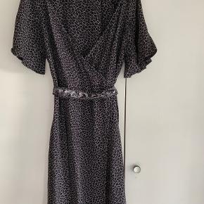 Super fin slå om kjole med palietbælte fra Noa Noa str. S. Kjolen falder rigtig fint og er i 100% viskose. Kjolen har stor vidde i nederdelen. Længde 98 cm. Kjolen er i meget fin stand. Fra ikke ryger hjem.