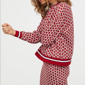 Sæt med nederdel og bluse i rød, guld og hvidt mønster med ribkant. Nederdelen er str. S og blusen er xs