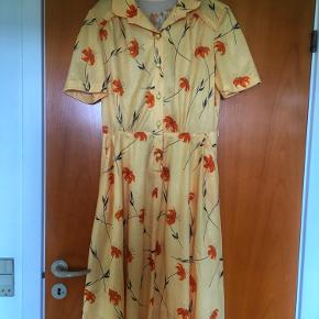 Skøn gul blomstret vintage kjole fra 70-80'erne. Kjolen er meget velholdt og har lommer. Mål: længde 105 cm. talje 2*38 cm, bryst 2*46 cm.