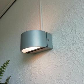 """Lumini """"Petit"""" væglampe Fra den Brasilianske producent Lumini   Perfekt stand Jeg har kun anvendt den indendørs  Ingen ridser eller anden slid. Lampen har næsten ikke været brugt  Lampen må bruges både ude og inde IP54  IP54/55 Støv- og spuletæt Dette betyder, at støv ikke kan trænge ind på elektriske komponenter, så der kunne opstå isolationsfejl.  Lyser op og ned  G9 50W pære medfølger  Halogen og LED kan anvendes  Materiale : Aluminium Farve : Titanium Satineret glas top og bund  Mål :  Bredde : 12 cm Dybde : 8 cm Højde : 6 cm.  Nypris kr. 1749 Sælges for kr. 1000  Lampen kan sendes for kr. 39  Du er selvfølgelig velkommen forbi"""