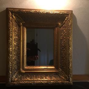 Firkantet spejl med meget kraftig guld farvet ramme med mønster.