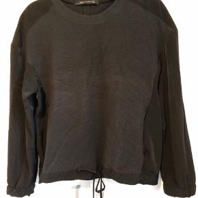Fed bluse i 2 forskellige typer stof med fine detaljer som elastik i ærmerne, bindebånd forneden.