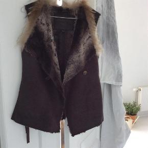 Varetype: Fair fur Størrelse: S (36/38/40) Farve: Mørk brun  Rigtig fin og blød vest fra Ilse Jakobsen. 2 sidelommer. Inder bindebånd ved talje.