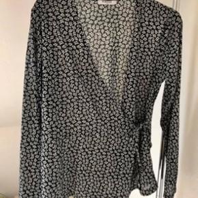 Fin slå-om bluse i grå-sort med hvide aftegninger. Aldrig brugt.