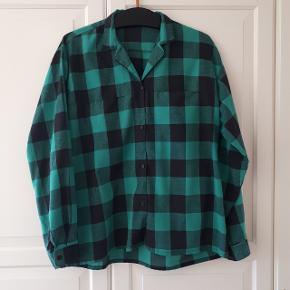 Grøn skjorte med to brystlommer foran, i str. L.  Måler ca. 58 cm fra ærmegab til ærmegab. Og ca. 66 cm fra skulder og ned.   Brugstegn ses i form af nuller (se sidste billede)  Hentes i Roskilde eller sender med DAO mod betaling af fragt.