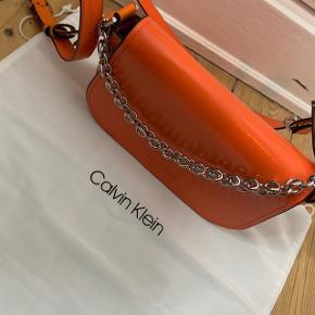 Lækker orange Calvin Klein taske. Np var omkring 1600kr. Umiddelbart ingen tegn på slidtage.  Dustbag følger med Hvis man ikke bryder sig om kæden kan den sættes om bagpå.