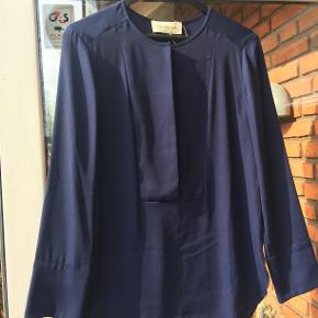 Smuk bluse med skjult lukning foran. 95% polyester.  Sendes for købers regning med DAO