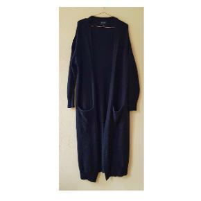 Lang cardigan med lommer. 17% Alpaca, 53% Acrylic, 30% Nylon.