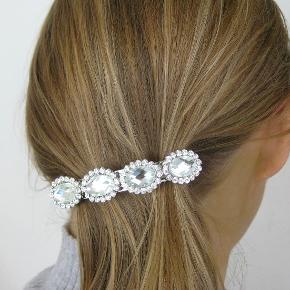 Elegant hårspænde med krystaller. Perfekt til festlige lejligheder og bryllupper. Måler 7,5 x 1,5 cm. Aldrig brugt og fejler intet.  Kan sendes med sporbar post til 36 kr. eller afhentes på Amager nær Amagerbro metro.