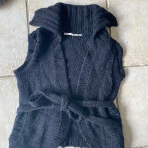 50% uld, 10% alpaka og 40% Acryl. Fantastisk blød og varm part two strik vest. Lommer foran og bindebånd i siden.  Str S. Np 800kr