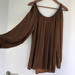 Smuk bronzefarvet silkebluse str 42 med snoet sort/sølv kant samt hul ved skuldrene. Mega smuk. Kan passes af M-XL, alt efter hvor oversized man ønsker den.   Farven ses bedst på billede 3 & 4
