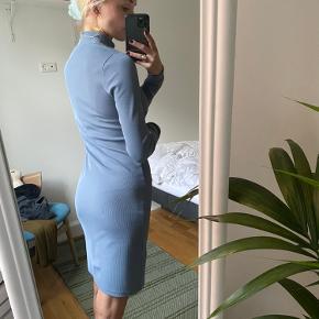 Fin kjole i smukkeste støvet blå farve. Brugt til arbejde. Ribbet stof og elastisk. Stoffet er ret lækkert - eksklusiv kvalitet.  Str 34, normal i størrelsen, men vil godt kunne passes af 36 også grundet elastik.   Har været virkelig glad for den, men fremstår som ny uden slid.