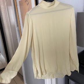 Smuk lysgul silkeskjorte. Der er kommet et par meget små pletter i kanten af skjorten, som kan ses på billedet. Kan fjernes ved at sende til rens. Bytter ikke