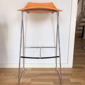Fin barstol med ben i stål og orange sæde i hård plast. Siddehøjden er ca. 75 cm.