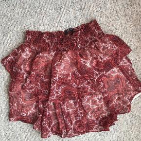 Blomstret rød nederdel fra Gina Tricot med elastik i livet og hvidt inderstof.   Den er lårkort, men længere bagved.  Passer en str. small/small