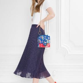 Parisian-chic navy midi skirt styled from a flowy pleated fabric. Featuring a waistband with concealed zip and button fastening