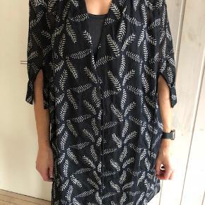 """Kimono, Munthe, str. 38, Sort m sølvmønster, Næsten som ny  Skøn kimino/kjole i spændende design fra danske """"Munthe"""".  Grundfarven er klassisk sort med et smukt bladmønster, hvor bladene er i sølvnuance afgrænset af en fin blålig kant. Er lettere gennemsigtig. 3/4 ærmer.  2 forskellige muligheder for at snøre ind i livet, så den kommer til at sidde til - og understøtte din figur. Kan således bæres på flere forskellige måder.  Mærke: Munthe Farver: Sort med bladmønster i sølv Størrelse: 38 (""""Modellen"""" på billederne er 175cm, 65 kg)  Nypris: 1.899 kr  Kun brugt 2-3 gange. Fremstår som ny."""