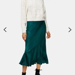 Flot satin nederdel i bias cut med flounce forneden. Har et meget smukt fald og shine. Aldrig brugt.