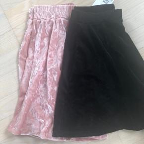 To velournederdele, den lyserøde er brugt en enkelt gang, den sorte er ubrugt. Den lyserøde 146-152, den sorte 158-164 i str (men den sorte er kortest i længden). Byd