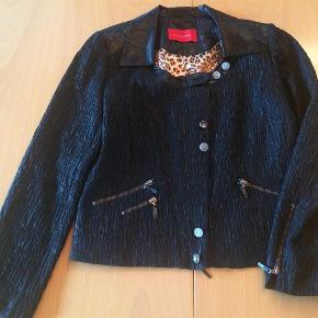 Varetype: Flot jakke med mange smarte detaljer Farve: Sort Oprindelig købspris: 2000 kr.  Jakken er brugt 2 gange og fremstår som ny.  Mål under ærmer: 2 x 49 cm  Mål fra krave til underste kant: 58 cm  Omkreds forneden: 98 cm