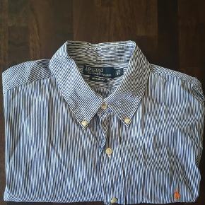 Varetype: Langærmet Farve: Mørkeblå,Blå Prisen angivet er inklusiv forsendelse.  Polo by Ralph Lauren blå/hvid stribet skjorte med orange logo sælges. Kun brugt 1 gang.  Str 17,5/44 Custom fit.  400kr inkl forsendelse ellers kom med et bud.