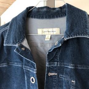 Super lækker jakke, der er perfekt til foråret og sommeren. Jakken er fra Calvin Klein Jeans og er i et blåt lidt fløjsagtigt materiale med en pæn overflade.   Jakken er egentligt en herremodel og størrelse S, men pasformen er mest som en M til kvinder - kan også passe en small for et mere oversize look.   Den er aldrig brugt og i perfekt stand.