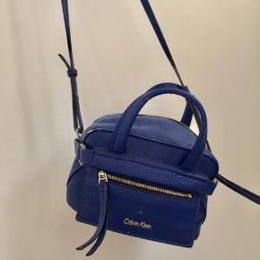 Blå Calvin Klein taske. Brugt med få slitager, men stadig super fin. BYD