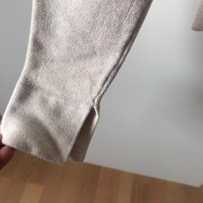 Cremefarvet cardigan med specielle knapper og strik samt lille slids ved ærmer. Virkelig fin cardigan.