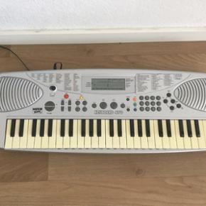Keyboard, Music Time 470  Det er meget velholdt og fungerer upåklageligt. Det har mange forskellige funktioner - bl.a. 30 forskellige stilarter, 50 forskellige stemmer og 50 forskellige sange. Der er mikrofon-indgang, høretelefon-udgang og MIDI-udgang.  Der medfølger 9 V adapter, men det fungerer også med batterier.