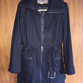 Zara Basic Lækker sort jakke med uld str 34.Brystvidde ca 2x 42 cm og længde ca 82 cm. Matr 55% uld, 29% polyester, 6% viscose og 5% nylon.