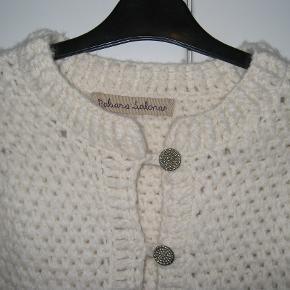 Fin kort cremefarvet strikjakke / cardigan i uld - lukkes med små sølvknapper  Brystmål ca 2 x 43 cm  Længde ca 52 cm målt fra kanten af halsudskæringen  Pris 400,-