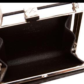 Varetype: Crossbody Størrelse: 10 x 12 x 2 Farve: Sort  Lille hardcase selskabstaske - model Ange pm - betrukket med sort silkesatin, et indvendigt rum samt lang skulderrem i metal.   Tasken er produceret i år 2001 - men har kun minimale brugsspor. Datakoden er SP0021.   Der er desværre ikke plads til en mobil tlf - er mere beregnet på mønter, kort og en læbestift.   Er vurderet hos Lauritz.com til kr 5.000,-   Prisen er fast, og jeg bytter ikke...