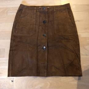 Klassisk ruskind nederdel med store lommer. Brug få gang da den er købt for lille.