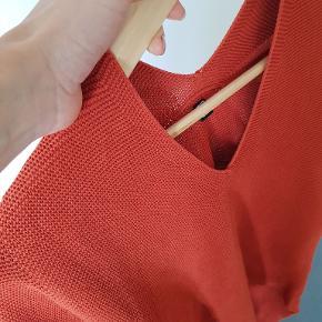 """Uniqlo strikket bluse i dejlig """"groft tekstur"""". Farve = støvet rød.  V-neck. Half sleves.  Har været glad for den, men skal have mindsket garderoben. God stand."""