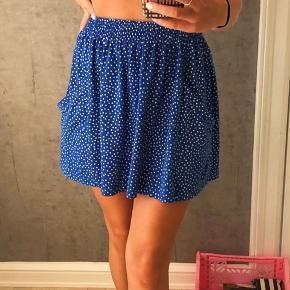 Fin blå og hvid prikket nederdel med elastik kant og lommer. Mærket siger str M, men kan sagtens passe en S. Perfekt til sommer 💙