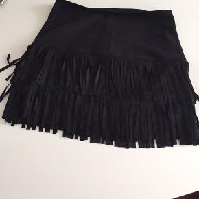 Sort lårkort nederdel med fast talje og 2 lag frynser, lynlås bagtil Måler i længde 41 cm fortil (med frynser 43 cm)