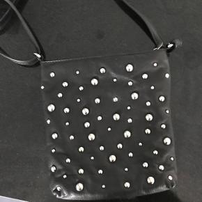 Lækker skind taske i sort læder med nitter ( sølv )Mål : 22 x 20 cm Brugt få gange - pæn stand og ingen slid eller lign.