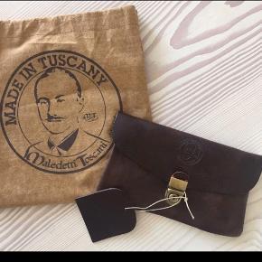 Flot ubrugt håndlavet cluthes i mørkebrunt læder;) -købt i Toscana -mærke: Maledetti Toscani. Kan sættes på et bælte;)  Np: 69 euro. Kommer fra røg frit hjem.