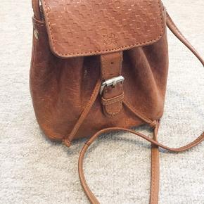 Boho taske fra Urban Outfitters i lysebrunt imiteret læder. Et stort rum og en lille inderlomme. Lukkes med snore og en trykknap