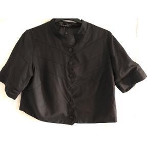Str. M. Kort jakke med glat foer. Brystvidde: 59 cm. X 2. Længde: 55 cm.