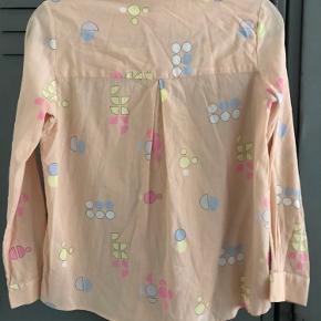 Fin tynd crepet skjorte i fersken/ nude farvet med mønster i forskellige farver. Den er brugt få gange og har ikke noget synlig slitage eller skrammer.