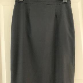 Smuk klassisk højtaljet nederdel med flot skåret linning bagpå (se foto).  Stoffet er i uld, polyester og elastan, så der er lidt stretch i. Hel-foret.   Meget fin stand, som ny.   Købt i 2018 for 1500 kr.