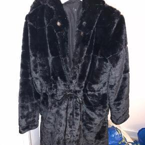 Fake fur frakke sælges. Blød og varm. Med lommer. Trykknapper og bindebånd. Hætte. Nypris 900kr  Sælger til højeste bud