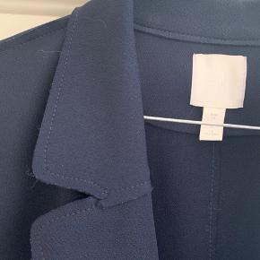 Mørkeblå navy oversize forårsfrakke i tyndt vævet bomuld med synlige syninger i kanten, se foto. 2 åbne lommer. Går ca. ned til knæene.  Brugt 3-4 gange, aldrig vasket. Alm i størrelsen.