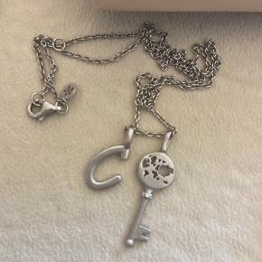"""Sælger denne fine halskæde fra ByBiehl, der medfølger kæde, to vedhæng, æske og kvittering   Det ene vedhæng er et """"C"""" og det andet er en nøgle med verdenskortet i.  Næsten ikke brugt og fremstår som ny!  BYD gerne ☺️"""