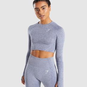 """Jeg sælger denne Gymshark Vital Long Sleeve Crop Top i farven """"Steel Blue"""", da den er en smule for stram til mig. Den er helt ny, stadig med mærke :)  Nypris: 350 kr."""