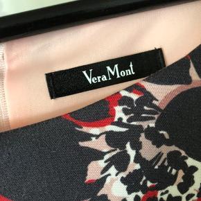 Smukkeste kjole fra Vera Mont i super lækkert stof. Kjolen er elegant figursyet med drapering over brystet og lynlås i ryggen. Flot rosa med mørkeblå/hvid/rød blomster på. Brugt 1 gang til konfirmation.  Str. 48 - men Vera Mont er ret lille i størrelserne (nok mere 44/46) Nypris kr. 1.599,- Sælges for kr. 380,- + Porto eller afhentet Odense S Betaling via mobilpay eller ts med gebyr lagt til.