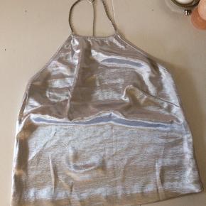 Halterneck top fra H&M i skinnende sølvfarve. Stropper i kæde, som kan åbnes og lukkes. Brugt få gange men har en lille plet foran. Passer en str M