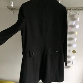 Margit Brandt frakke i str.L. Sort. 60% uld/30 % polyester. Lukning foran skjuler knapper. M.små inderlommer